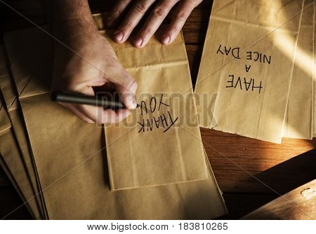Hands Writing Thankful Words on Paper Bags