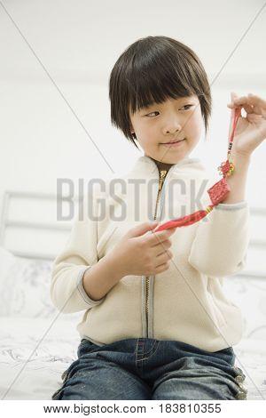 Chinese girl holding tassel
