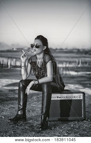 A brutal girl smokes a cigarette while sitting on the amplifier. The rock star after a concert has a rest and enjoys the nature.