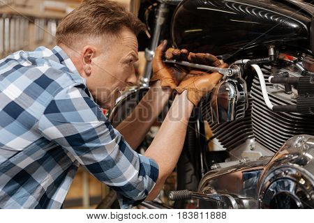 Being careful. Gifted successful diligent serviceman using special tool for drawing up a bolt on his bike while repairing it
