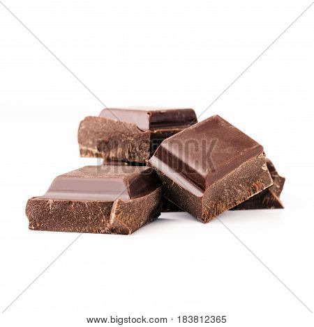 Pieces of bitter dark chocolate bar cubes on heap isolated on white background close-up view.