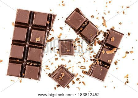 Pieces of dark chocolate bar cubes sprinkled with grated chocolate isolated on white background top view.