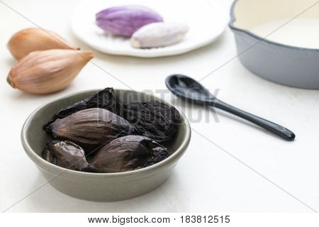 Close up of black fermented onions in a dish with a bright out of focus background to ad copy space