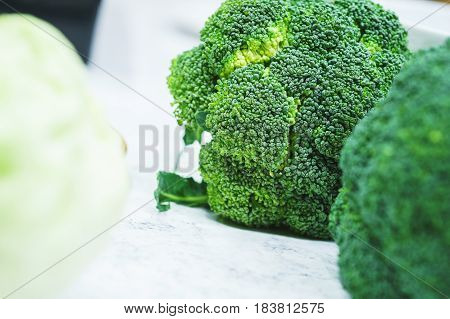 Pure fresh broccoli prepared for cooking vegetarian dishes in the kitchen. Fresh vegetables for healthy eating. Preparation and cooking of healthy food. Soft focus.