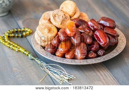 Close Up Of Dried Date Fruits Or Kurma And Figs Served On A Old Vintage Plate With Ornaments And Bea