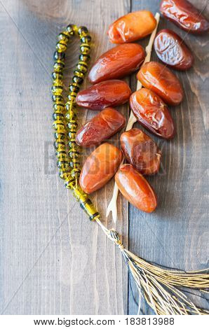 Dried Date Fruits Or Kurma And Beads On A Wooden Background, Ramadan Food Concept. Close Up. Copy Sp
