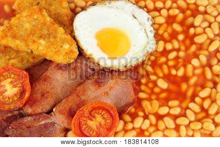 Bacon and egg breakfast meal with hash browns and baked beans in tomato sauce