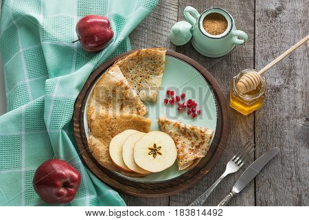 Tasty traditional russian breakfast of pancakes with honey on plate. Rustic style.