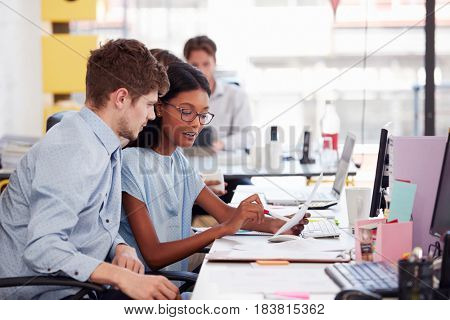 Young man and woman working together in an open plan office