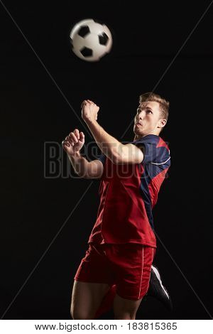 Professional Soccer Player Jumping To Head Ball In Studio