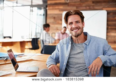 Young casually dressed white man in office looking to camera
