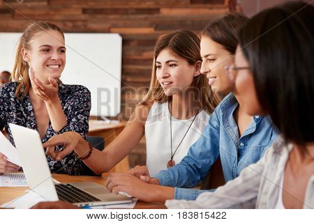 Four female colleagues looking at computer in an office