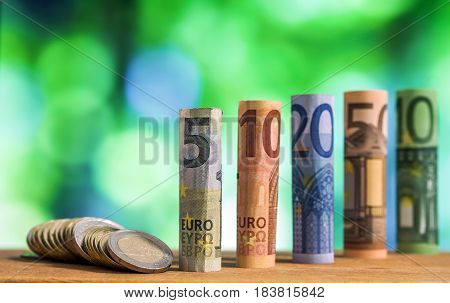 Five, Ten, Twenty, Fifty And One Hundred Euro Rolled Bills Banknotes, With Euro Coins On Green Blurr