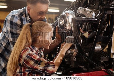 Be careful here. Charming active attentive girl being fascinated by all mechanisms while assisting her dad repairing the bike