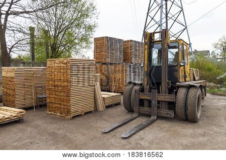 Large lift truck and stacks of new wooden boards and studs at the lumber yard. Wooden plates on piles for furniture materials