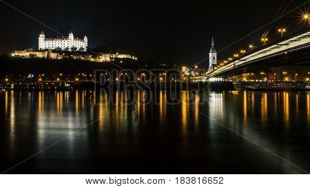 Night scape of the city of Bratislava from the opposite side of the Danube. Bratislava castle St. Martin's Cathedral and the UFO bridge all pictured.