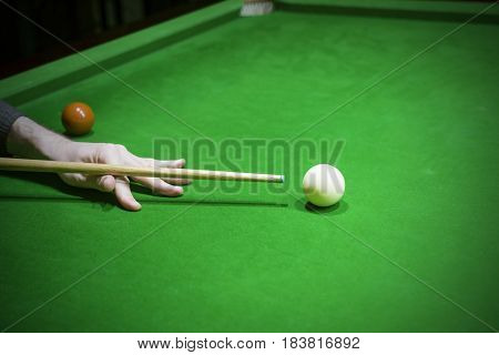 Snooker table. Player aiming the cue ball.