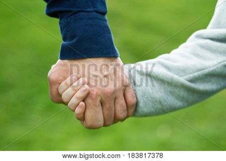 Hands. Father's and his son hands. Dad leading son over summer nature outdoor. Male and children hands closep. Family, trust, protecting, care, parenting concept.