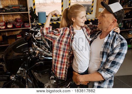 I am a big girl now. Passionate stubborn eager child trying persuading her dad she being strong enough by demonstrating her biceps