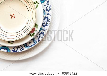Stack of empty ceramic plates isolated on white background with copy space. Cheerful colorful dishes decorated with floral pattern. Beautiful vintage crockery top view close-up