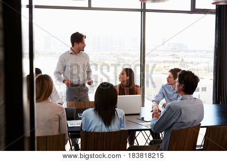 Young man with documents addresses team at boardroom meeting