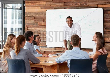 Young black man stands addressing colleagues at a meeting