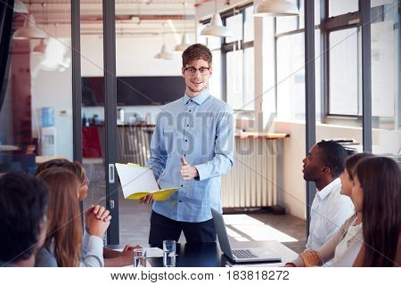 Young man holding document addressing colleagues at meeting