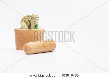 Mortar made of tropical wood and us dollar banknote on white background.