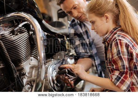 It is greasy. Supportive loving nice father asking not touching dirty parts of the motorcycle while his daughter helping him with repairing