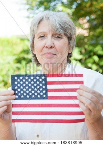 Senior woman holding US flag