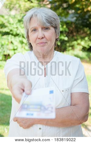 Senior woman hands out 50 euro note