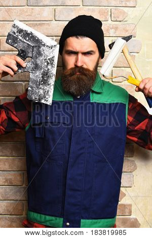 Bearded Builder Man Holding Various Building Tools With Serious Face