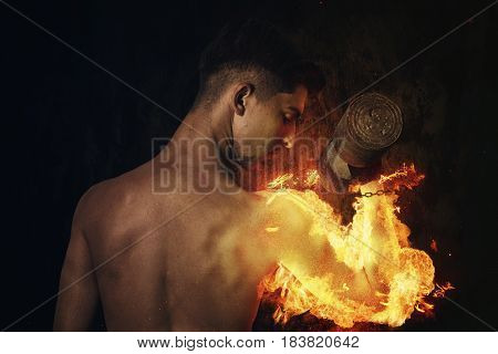 power athletic young bodybuilder doing exercises with fire hand