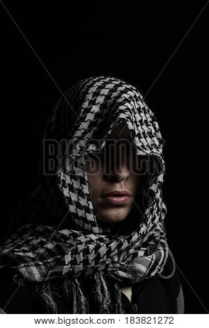 hidden man with palestinian scarf over head in front of isolated black background
