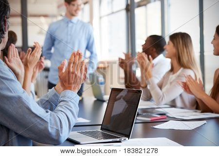 Business team applauding colleague at a meeting