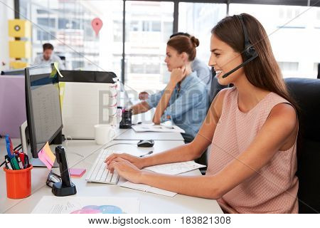 Young woman wearing headset using laptop computer in office