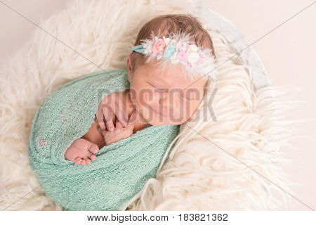 Adorable cute baby smiling in her sleep, hairband with flowers, wrapped tightly, closeup