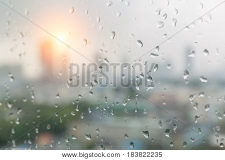 Rain drops on window glass and blurred cityscape and sunlight in background.
