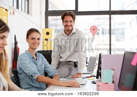 Young man and woman in open plan office looking to camera