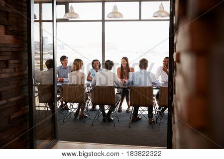 Team in a boardroom meeting seen through open doors, full length
