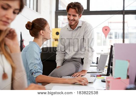 Young man sits on woman's desk talking in open plan office