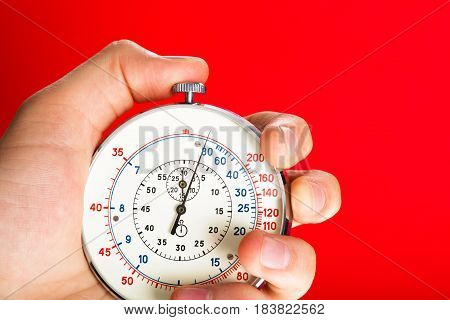 Close Up Of Hand Holding Stopwatch on Red Blackground