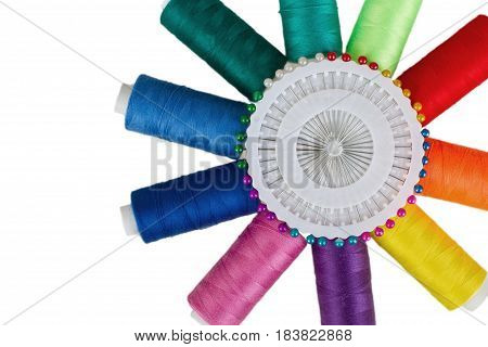 Multicolored spools of thread with sewing pins in a holder