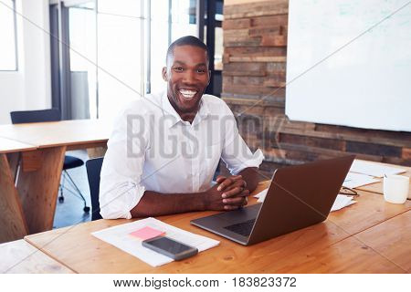 Young black man at desk with laptop computer looks to camera