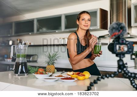 Young Woman Recording Content For Her Video Blog In Kitchen.