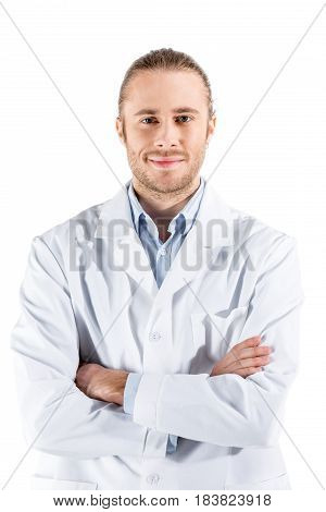 Young Doctor In White Coat With Crossed Arms Looking At Camera Isolated On White