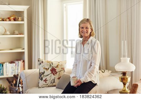 Senior woman looking relaxed and happy in her lounge at home, sitting on the edge of the  arm of her couch holding a coffee cup