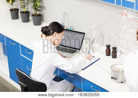 High angle view of young scientist using laptop and writing in clipboard in research laboratory
