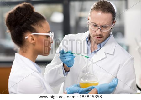 Side View Of Concentrated Scientists Making Experiment In Laboratory