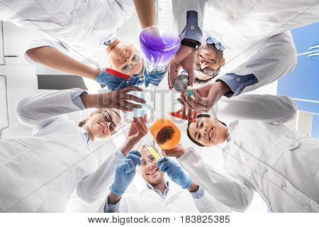 Low Angle View Of Scientists Holding Various Test Tubes